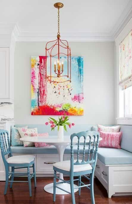 a small round white table matches a light blue upholstered bench and chairs