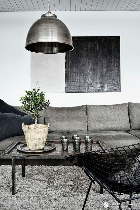 upholstered grey sofa with navy pillows and an echoing lamp