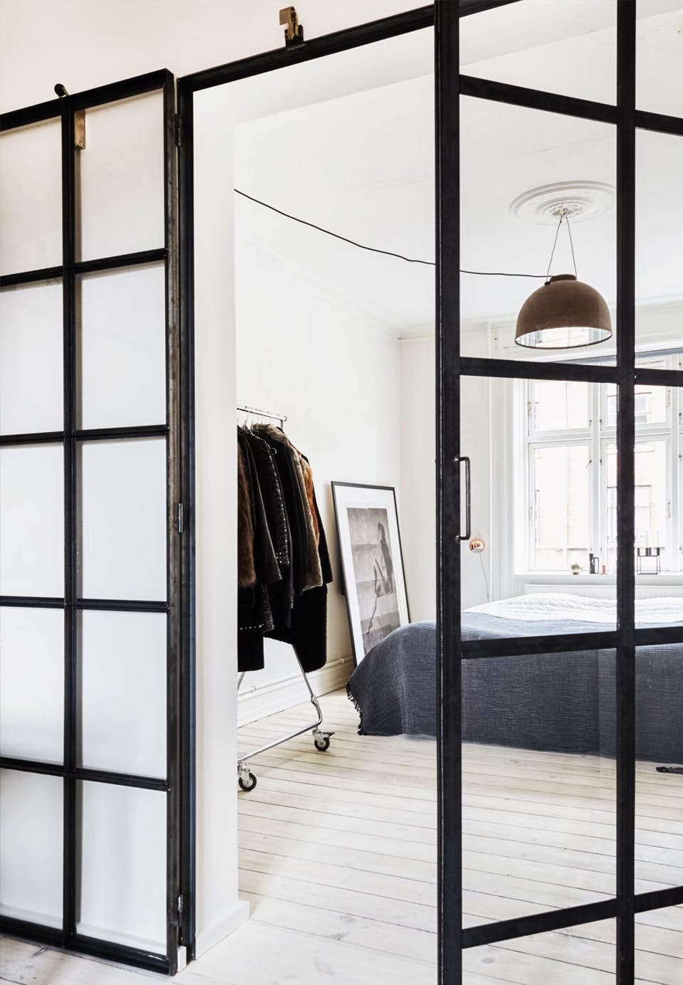 Black metal framed glass doors separate the bedroom from the rest of the apartment, they let light in and look lightweight