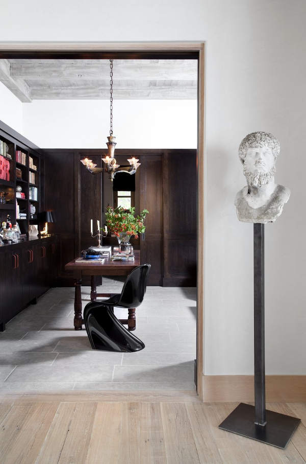 The home office is clad with dark wood, there are traditional shelves and a desk but a modern twisted chair