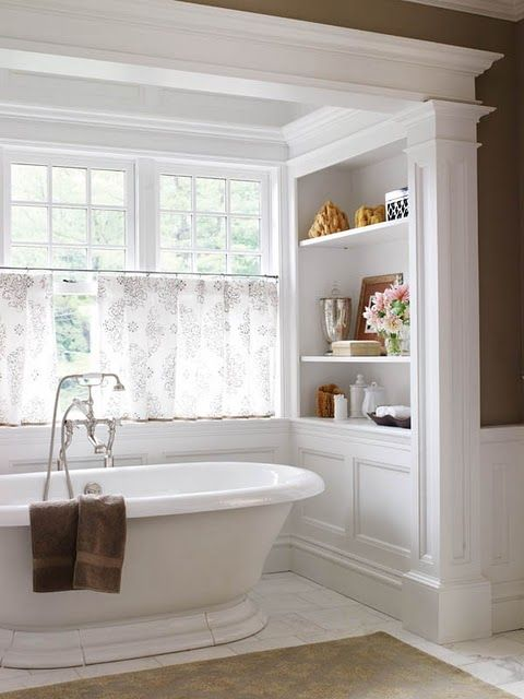 a cool freestanding tub in a niche, half curtains for privacy and shelves on each side of the bathtub
