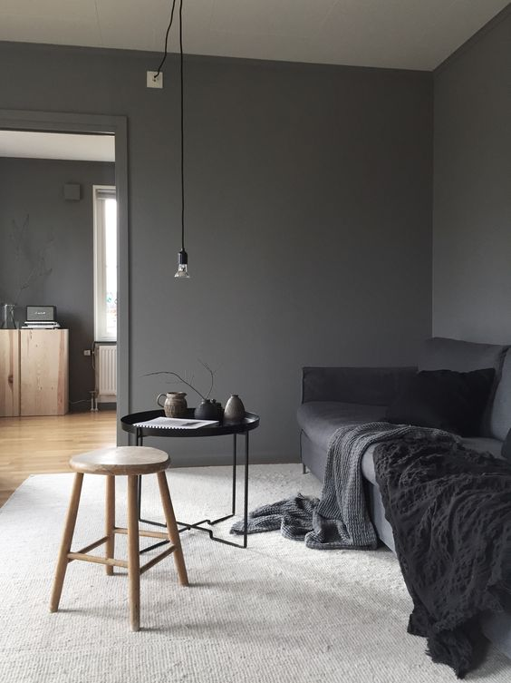 a dark grey sofa is a focal point in this moody space