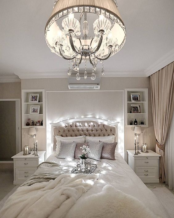 a neutral and refined bedroom with a vintage-inspired chandelier with crystals and a fabric lampshade