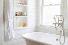 06 all-white bathroom with wooden floors for a rustic feel, a white tub with white legs