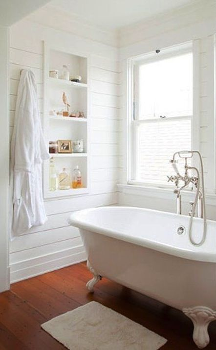 all-white bathroom with wooden floors for a rustic feel, a white tub with white legs