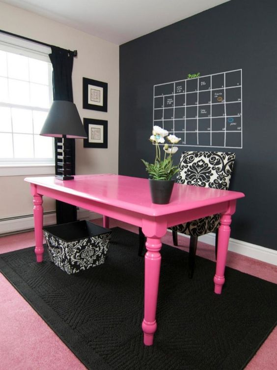 bold pink desk in a black home office makes a statement