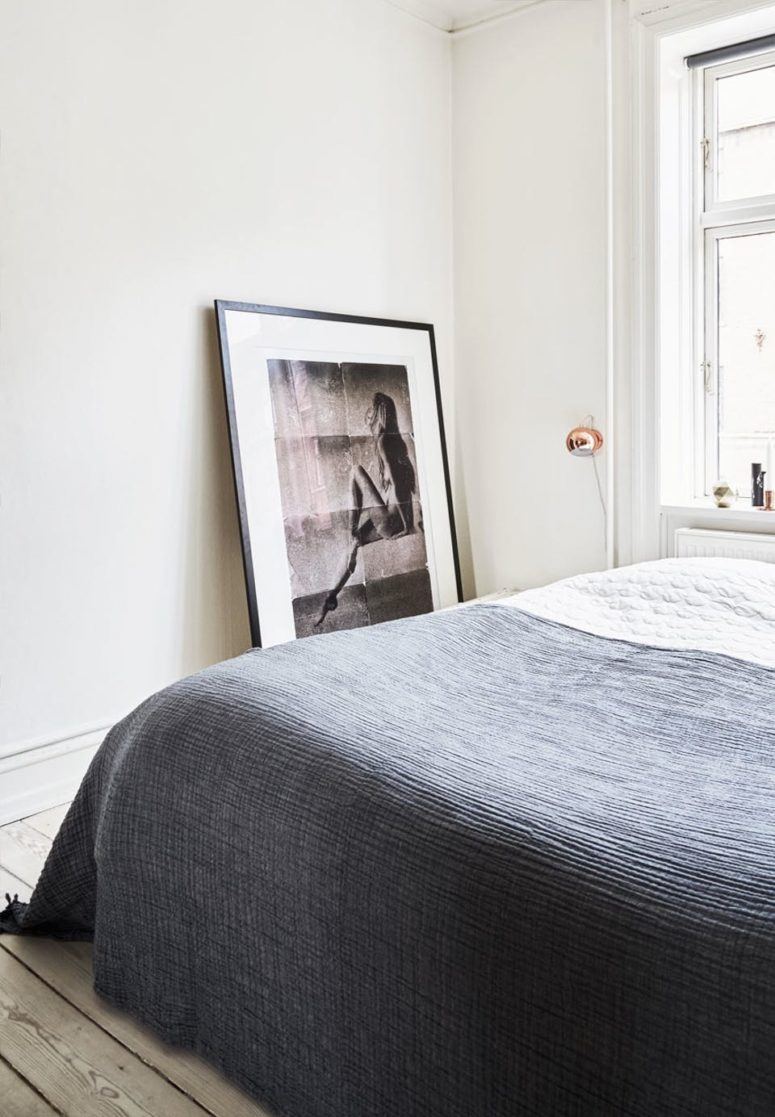 A large bed in placed next to the window, an oversized photo adds an artistic feel
