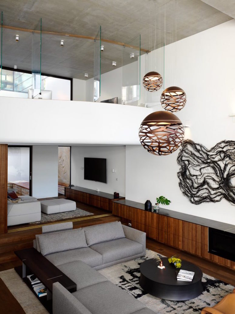 Glass partitions enclose the upper level of the house, exposing it to the ground floor spaces