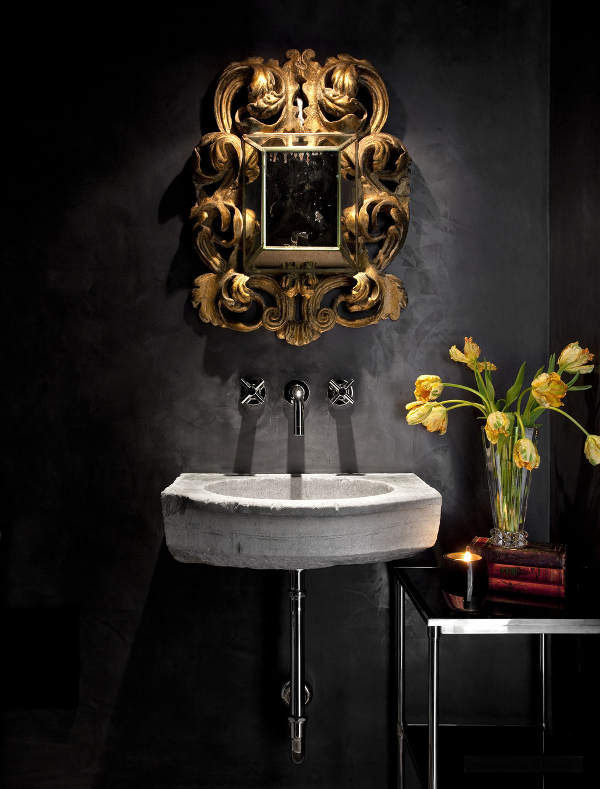 The bathroom is done in black, with a concrete sink and a refined gold frame mirror