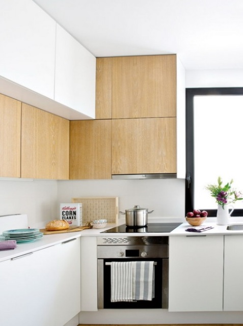 The kitchen has white and light colored wooden cabinets with no handles for a neat look