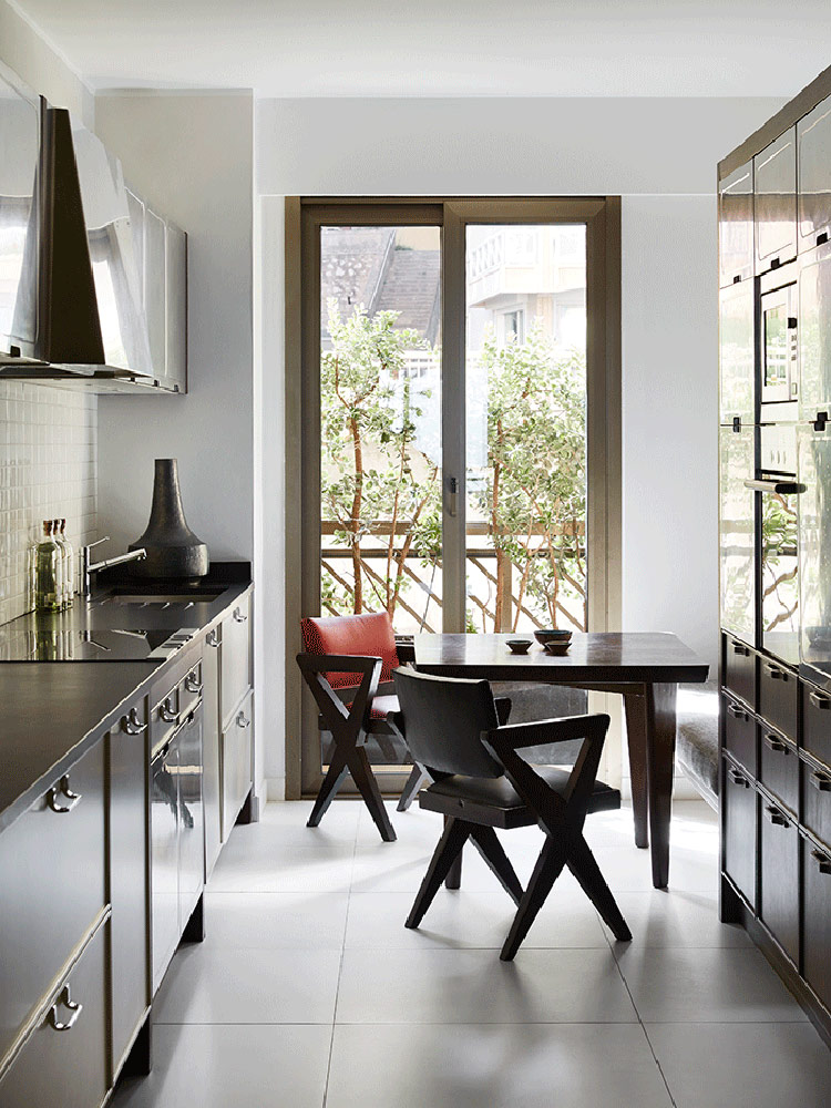 The kitchen is a dark mid-century modern one, with dark cabinets and a breakfast nook next to the glass door to the terrace