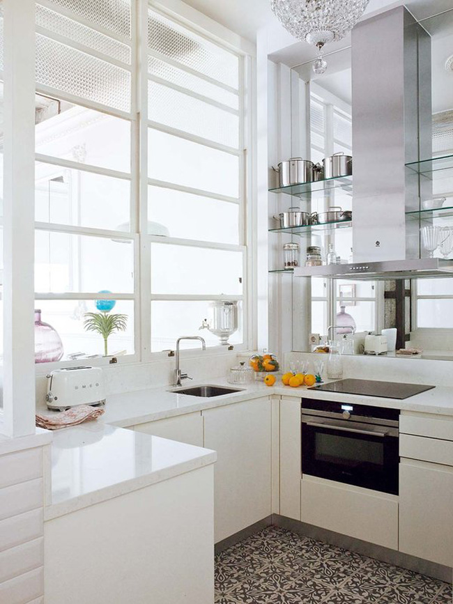 The kitchen is all white, it's modern and laconic, and a mirror wall make it look bigger