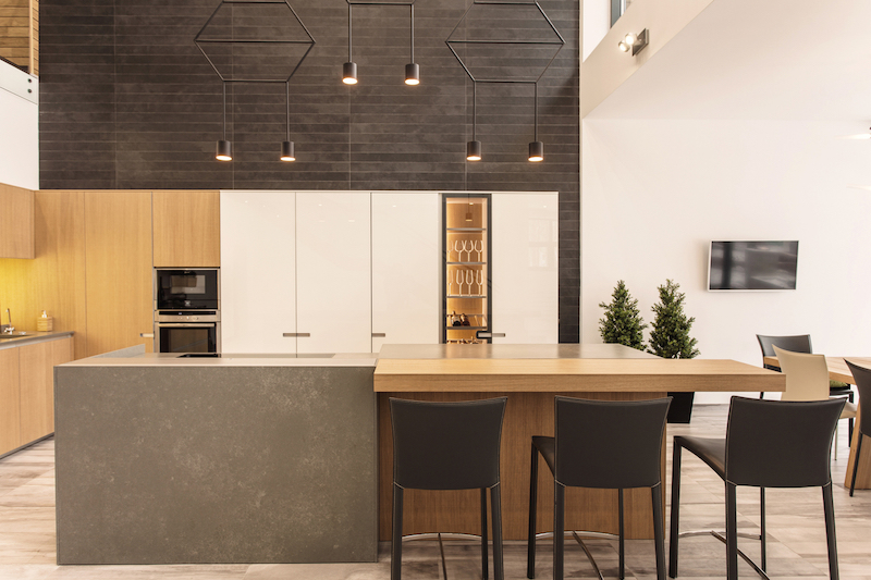 The kitchen island is simple and robust and features a wooden bar extension