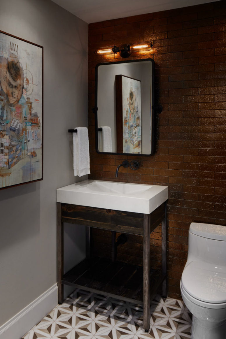 The powder room is decorated with graffiti, there's a dark tile wall and a stained wood sink stand
