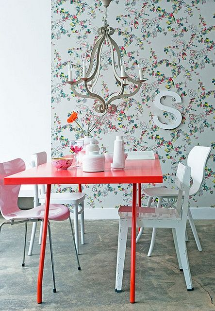a cute red dining table and a blush chair make the space girlish