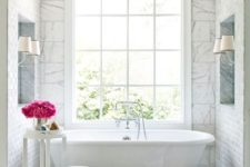 07 a glam bathtub niche with marble tiles, a flower stand and a large window for a cool view
