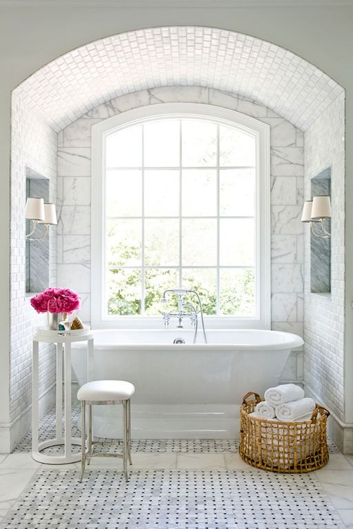 a glam bathtub niche with marble tiles, a flower stand and a large window for a cool view
