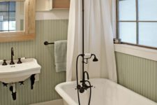 07 vintage-inspired bathroom with a clawfoot tub and black accents to pull everything off