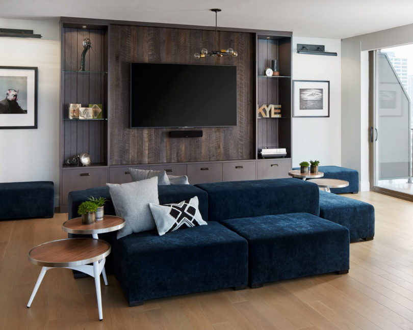 I totally love this navy velvet sofa with poufs that will accomodate all the guests, and a reclaimed wood TV unit with shelves