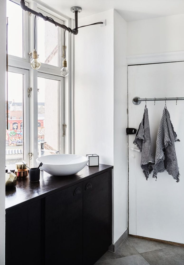 The bathroom shows black cabinets, and the sink is right next to the window to save the space and enjoy the view