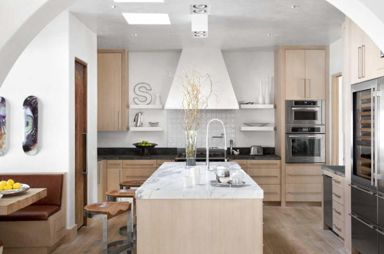 The kitchen is done in white and light-colored wood, I love the refined marble touches