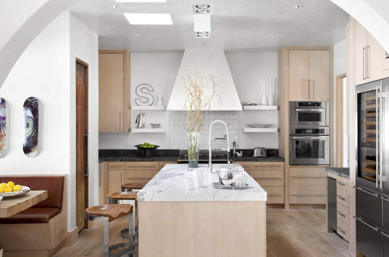 The kitchen is done in white and light colored wood, I love the refined marble touches