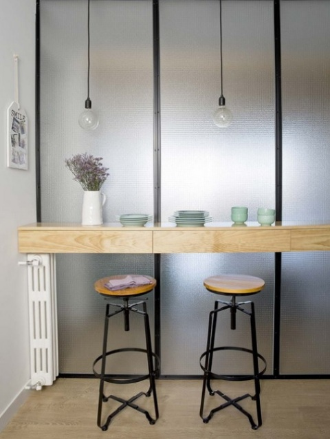 There's a breakfast nook with a wooden countertop and bulbs over the it for more light