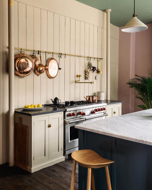 There's a creamy wall covered with wood, with several cabinets of the same color and a holder with copper pans