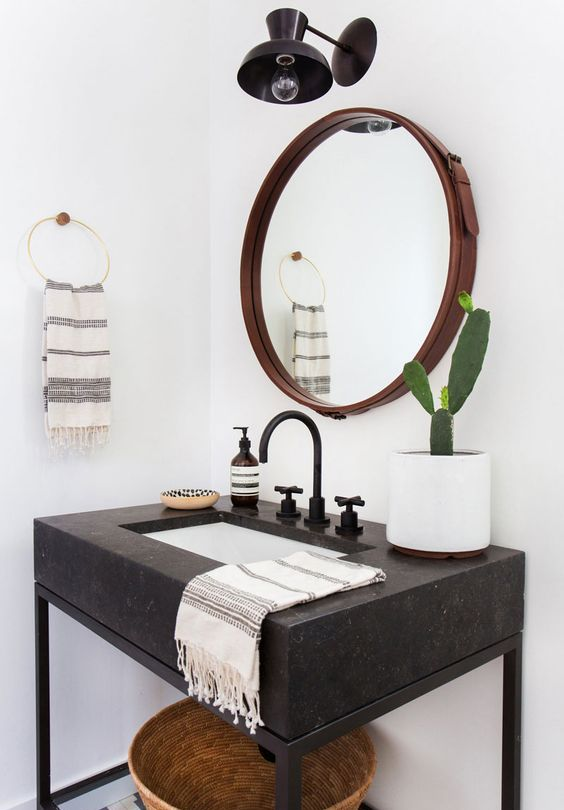 a black Corian and metal bathroom vanity with a shelf underneath