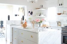08 a modern glam kitchen with a tall hanging chandlier with brass details and sheer crystals