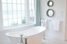 08 a modern soothing bathroom with aqua touches and a freestanding tub next to the window