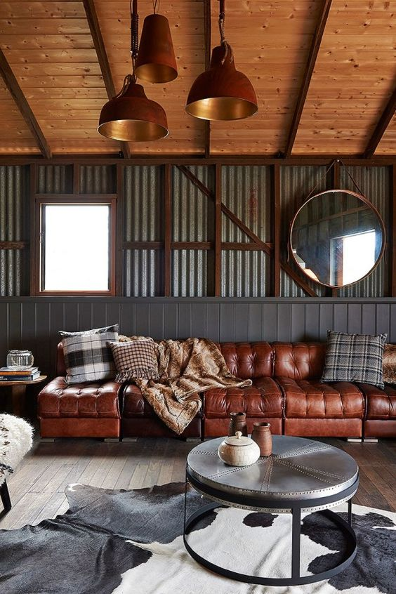 an industrial themed living room with a sofat brown leather sofa