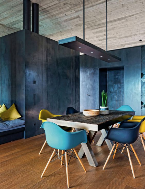 rustic X leg dining table looks unusual with modenr colorful chairs and a pendant lamp