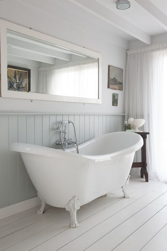 serene bathroom with a white bathtub on clawfoot legs and whitewashed wooden floors