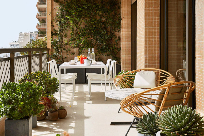 An outdoor dining zone is a dreamy one, and there are some wicker chairs to relax