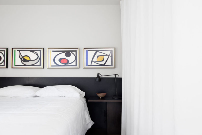 The bedroom features a dark colored bed and abstract artworks