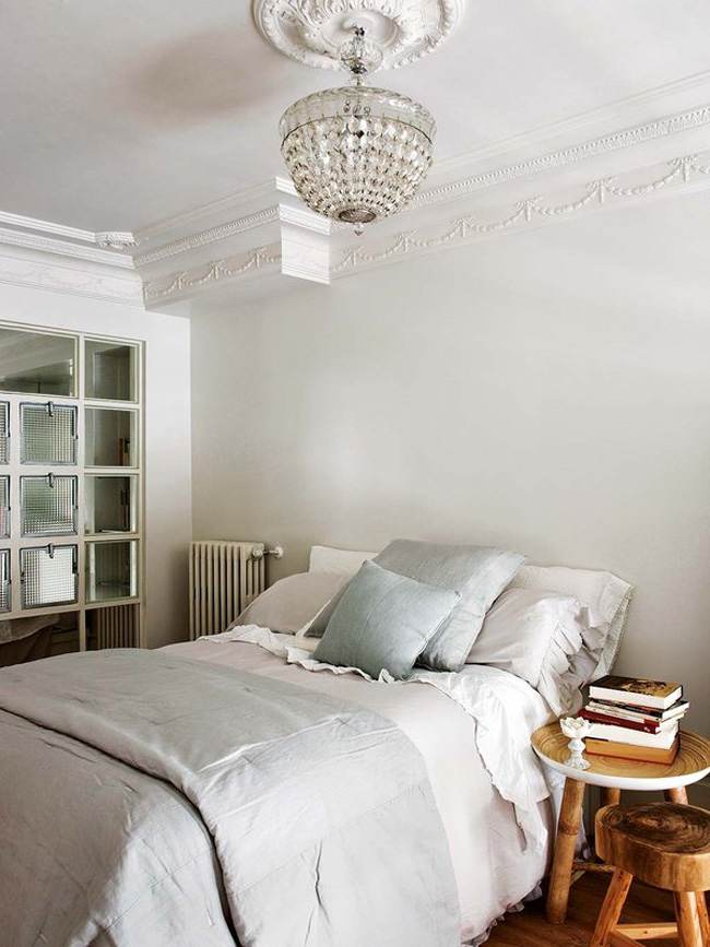 The bedroom is vintage, with molding, rustic stools and a glazed wall