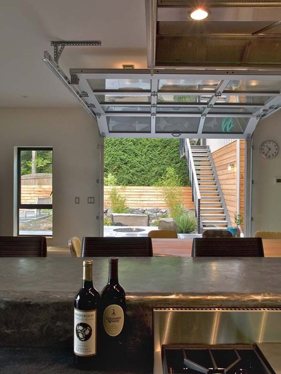 a glass-paneled garage door virtually eliminates the division between the main room and an outdoor living area