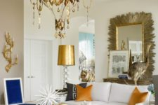 09 a whimsy living room with a chic brass chandelier and gold hanging details