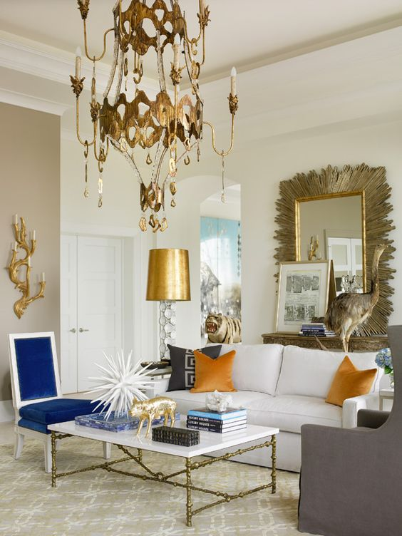 a whimsy living room with a chic brass chandelier and gold hanging details