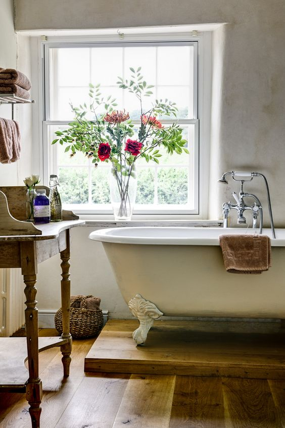 rustic bathroom with an ivory bathtub with white legs on a wooden stand