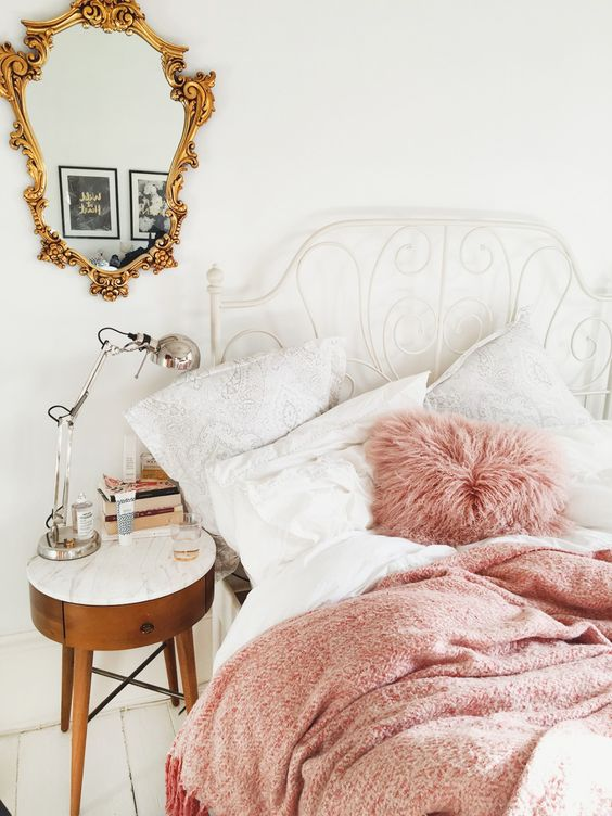 white metal bed with a curling headboard and pink bedding