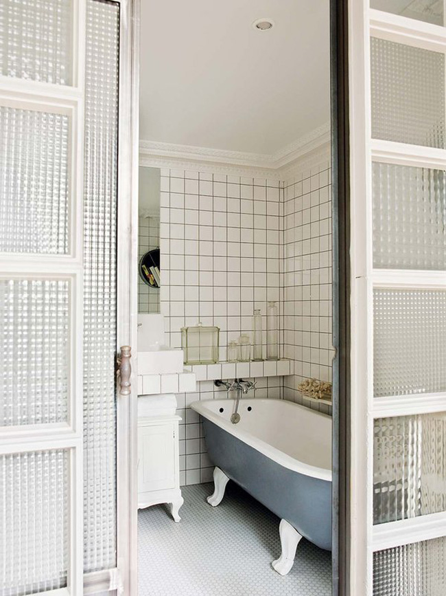The bathroom features subway tiles, a free standing blue bathtub