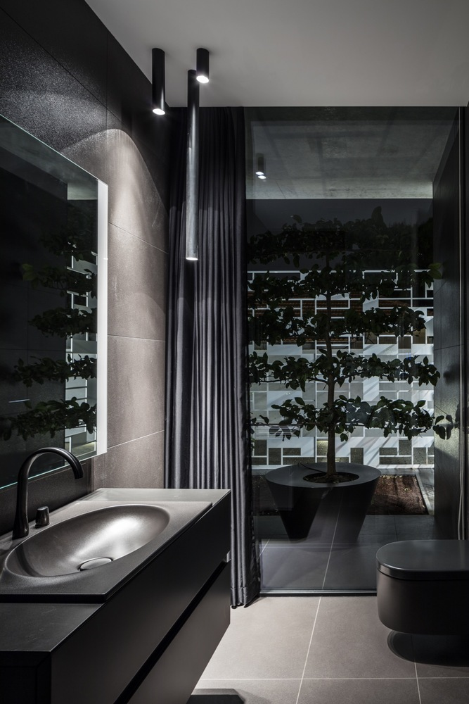 The bathroom is dark and moody, with a tree and dark walls and appliances