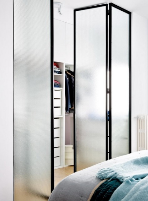 The closet is separated with foldable frosted glass doors that save the space