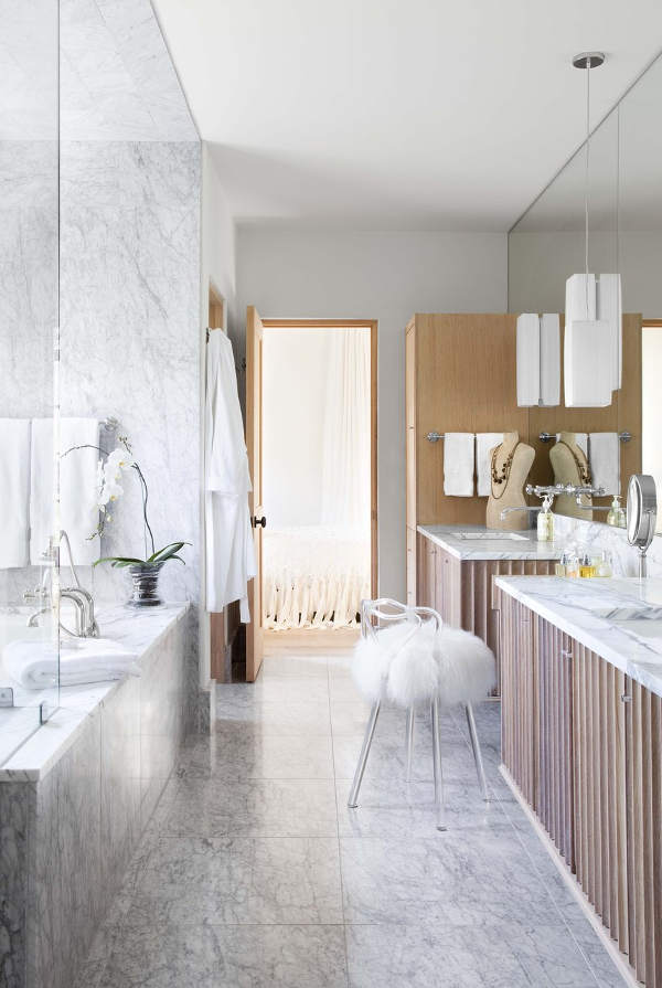 The master bathroom is clad with white marble and light-colored wood, I love glam accents