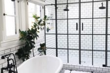 10 a freestanding tub is connected to the shower with a black faucet and a black glass pendant lamp over it