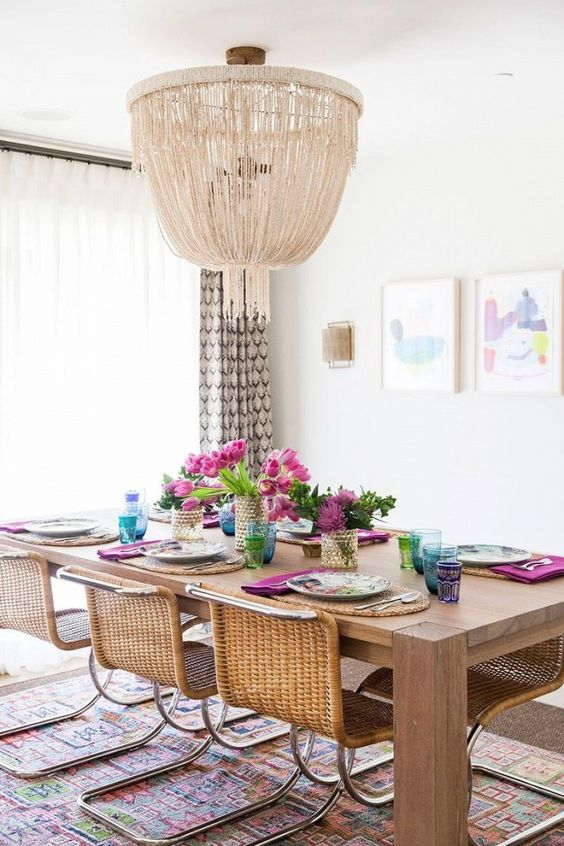 a modern boho dining space with wicker furniture and a large glam chandelier