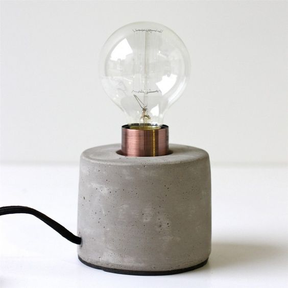 a table lamp with a concrete base and a bulb looks simple and laconic