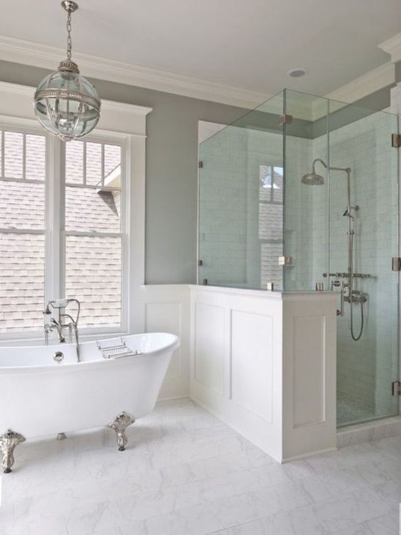 vintage-inspired bathroom in neutral colors with a white clawfoot bathtub on silver legs